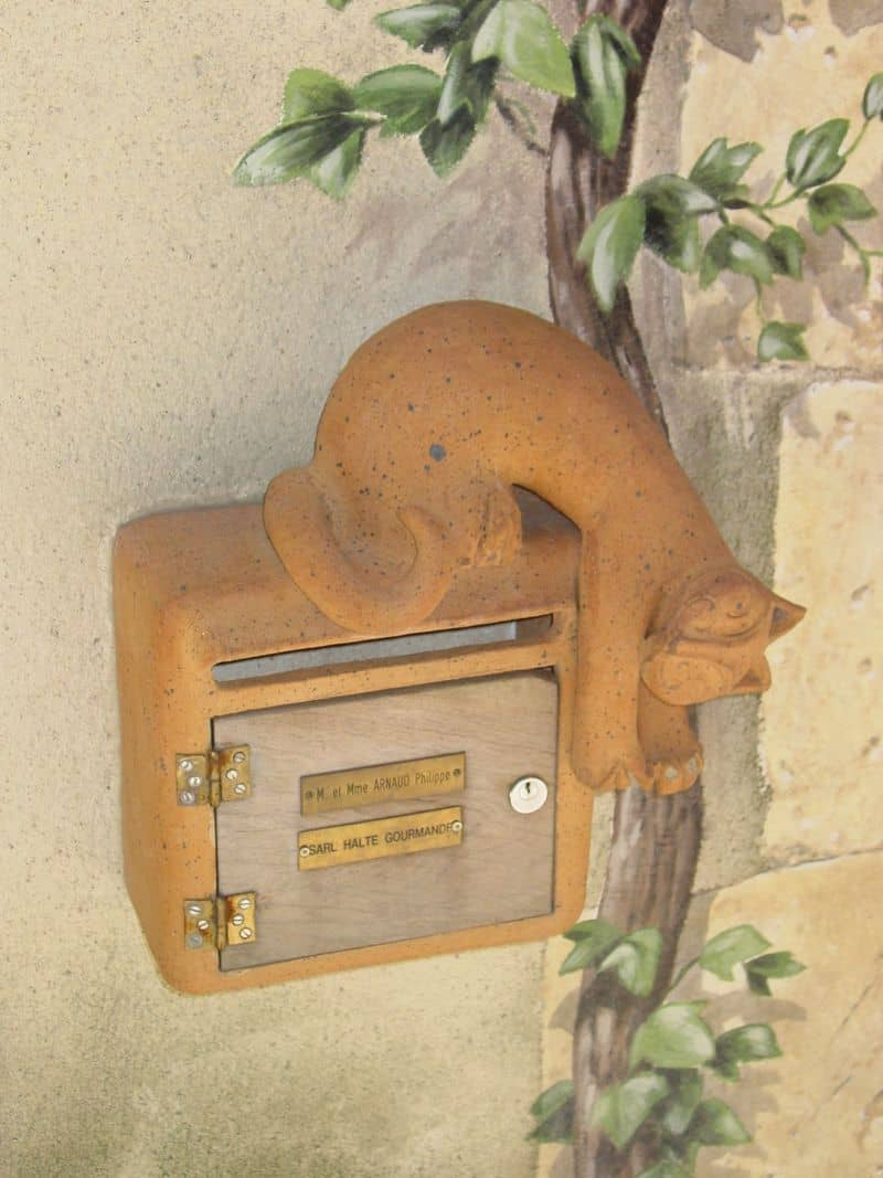 A not so ordinary mailbox with a playful kitty daring you to put the mail in.